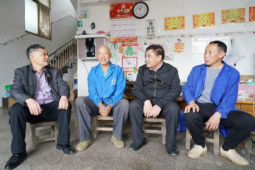 2021年2月3日上午,曾馥平(右二)与河池市环江毛南族自治县思恩镇三乐村肯福科技扶贫示范区的村民们话家常,了解他们的生产生活情况。记者 周剑峰 摄_副本.jpg