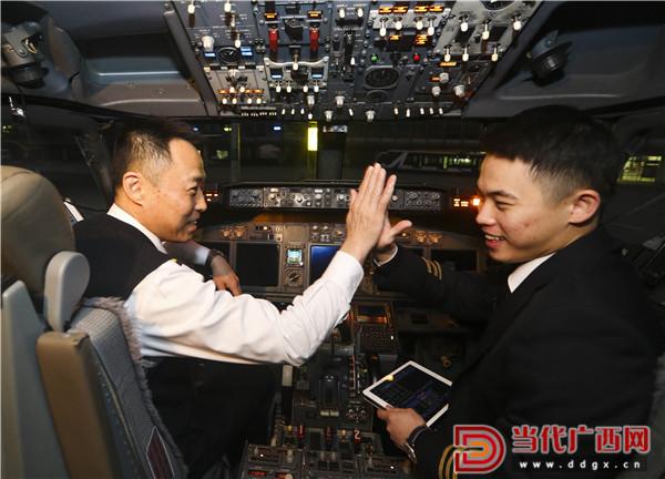 1月28日,左志强(右)和左炀在驾驶波音737—700飞机前击掌,准备飞往福建福州。 记者 刘峥 摄.jpg