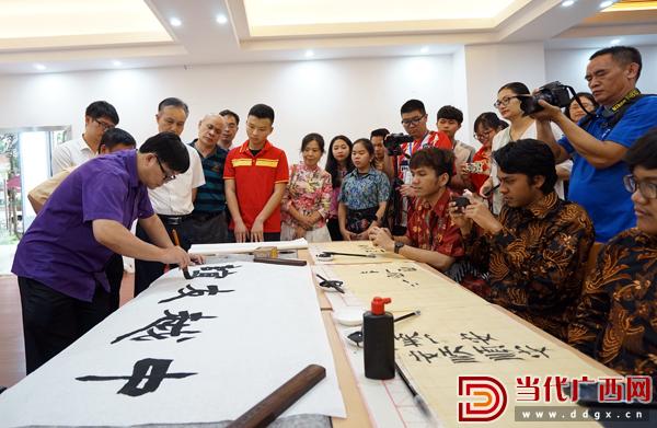 中国书法家协会会员、广西书法家协会副主席韦渊为外国留学生展示中国书法。记者 李姣梦 摄.jpg