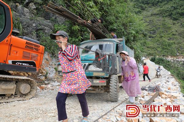 村民将建材搬下货车后再用三轮车转运至屯内。张友豪 摄_副本.jpg